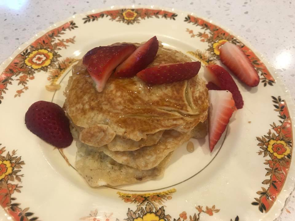 gluten-free, dairy-free pancakes with strawberries and maple syrup